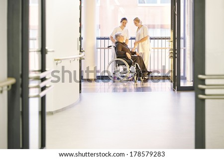 Patient in the hospital with nurses and wheelchair - stock photo