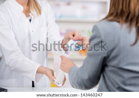 Patient pays for the medicine to the pharmacist with a twenty euro note while receiving the bag - stock photo