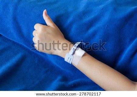 Patient's arm in hospital. shoot on blue blanket background - stock photo