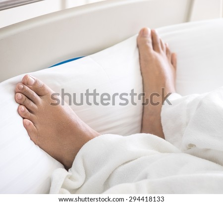Patient's feet on bed in hospital for medical background - stock photo
