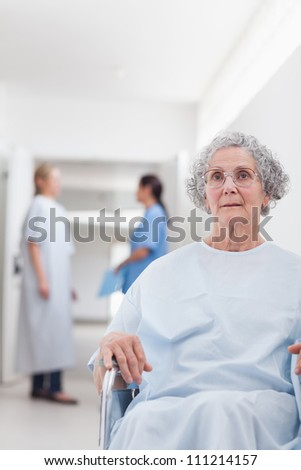 Patient sitting in a wheelchair in hospital ward - stock photo
