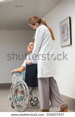 Patient sitting on a wheelchair looking at a doctor in hospital ward - stock photo