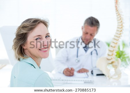 Patient smiling at camera in medical office - stock photo