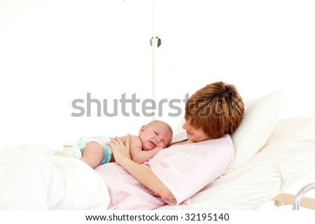 Patient speaking to her newborn baby in bed in hospital - stock photo