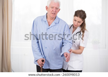 Patient using walking stick assisted by doctor - stock photo