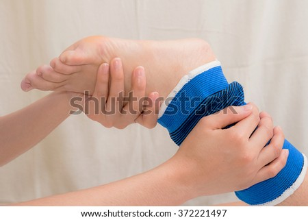 Patient with ankle sprain using ankle support stabilizer after rehabilitation - stock photo
