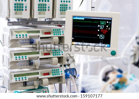 Patient with monitor and infusion pumps in an intensive care unit - stock photo
