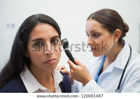 Patients ear being checked by doctor using otoscope in hospital - stock photo