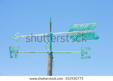 Patina green rusty old weather vane isolated on summer sunny blue sky background, with arrow and symbols for direction, copy space. - stock photo