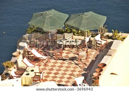 patio and green parasols over the caldera on Aegean sea, Oia village, Santorini, Greece - stock photo