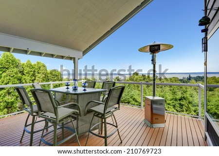 Patio area with table, chairs and heater on walkout deck overlooking scenic view - stock photo