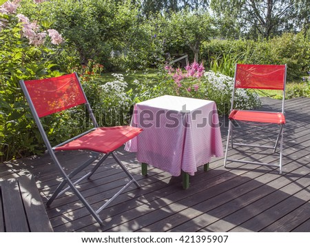 Patio furniture on a balcony. Garden, flowers in the background. - stock photo