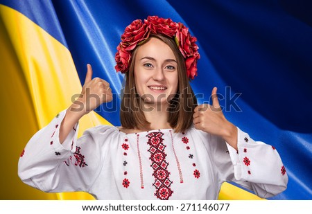 Patriotic concept. Happy young girl in the Ukrainian national suit against Ukrainian flag background - stock photo