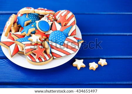 Patriotic cookies for 4th of July on a blue wooden background in a white plate. With scattered stars. - stock photo