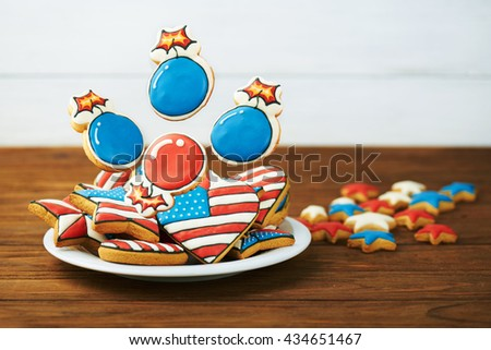 Patriotic cookies for 4th of July on a wooden background in a white plate. With scattered stars.  - stock photo