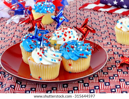 Patriotic cupcakes in a festive celebratory table setting.  Great for July 4th, Memorial Day or Veterans Day. - stock photo