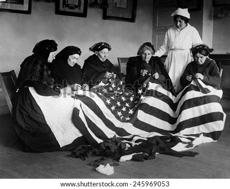 Patriotic elderly immigrant women making a flag during WWI. They are from Eastern Europe countries of Hungary, Galicia, Russia, Germany, and Rumania. Ca. 1918. - stock photo