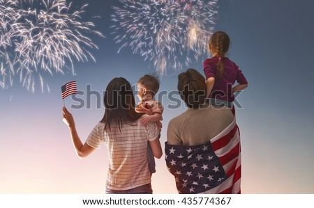 Patriotic holiday. Happy family, parents and daughters children girls with American flag outdoors. USA celebrate 4th of July. - stock photo