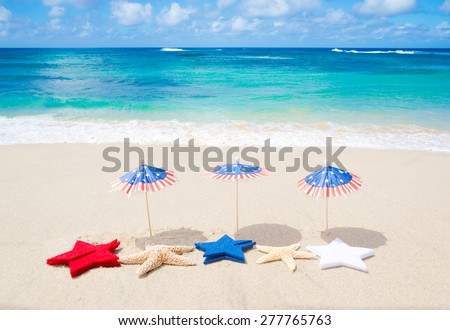 Patriotic USA background with starfishes and decorations on the sandy beach - stock photo
