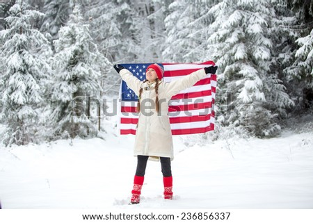 Patriotic young woman with the American flag held in her outstretched hands in winter landscape. daylight - stock photo