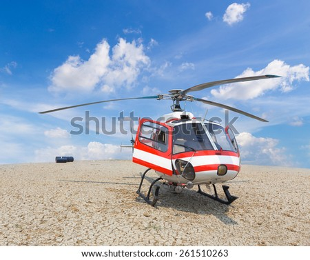 patrol helicopter of firefighters landing on the crack floor with blue sky - stock photo