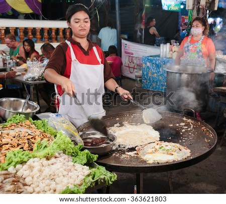PATTAYA, THAILAND - APRIL 4, 2015: Woman in a street cafe fry food - stock photo