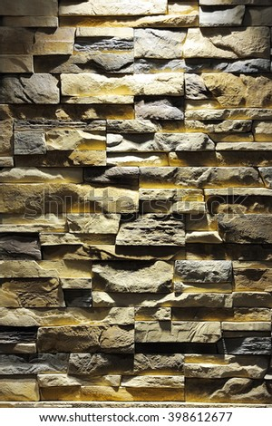 pattern of decorative brown grey slate stone wall surface, lit by a spotlight - stock photo