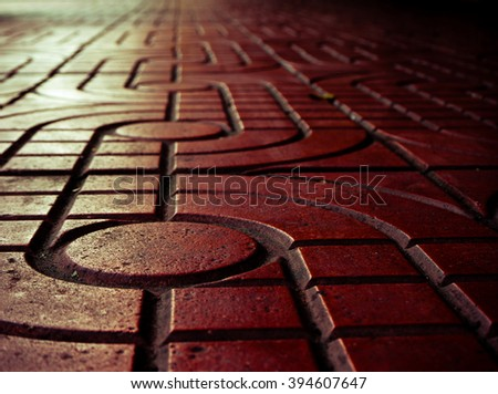 Pattern of sidewalk. Red pattern street road. Sidewalk, pavement texture. Yellow light reflection. - stock photo