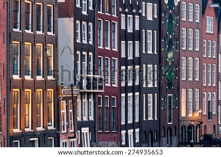 Pattern of windows, compressed tightly by telelens, of traditional quaint houses in Amsterdam, capital of Holland, Netherlands, showing irregularities in the construction of these vintage buildings - stock photo
