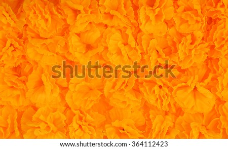 Pattern pile of yellow artificial marigold flowers for texture and background - stock photo