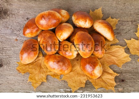 patties meat or cabbage on autumn leaves on the wooden background - stock photo