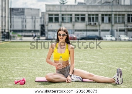 Pause in fitness training. Girl with dumbbells sitting on field holding a bottle of water and drinking water - stock photo