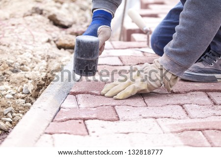 Pave bricks setting by rubber hammer - stock photo