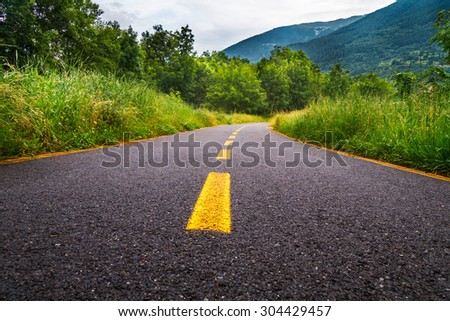 Paved cycle lane with yellow path - far destination - stock photo