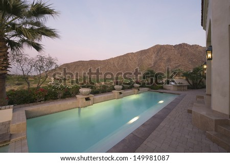 Paved poolside area of home against mountain and clear sky - stock photo