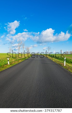Paved road through flat landscape on sunny day in winter - stock photo