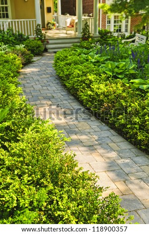 Paved stone path in lush green home garden - stock photo