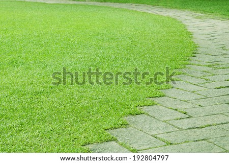 Pavement made of stone in green grass - stock photo