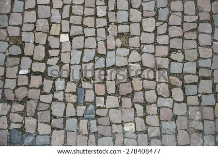 Pavement of grey and pinkish foursquare-similar cobblestones as background. - stock photo