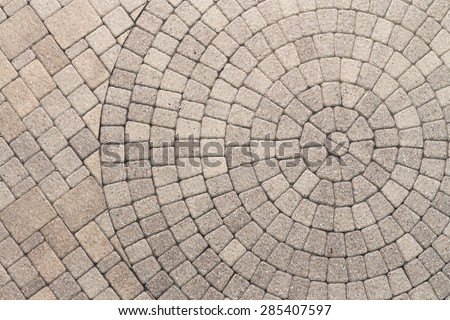 Paver bricks arranged in a circular pattern of concentric geometric circles. Architectural background of an ornamental pattern in outdoor patio paving. - stock photo