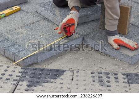 Paver measuring irregular space for laying concrete brick, laying cement blocks. Selective focus. - stock photo