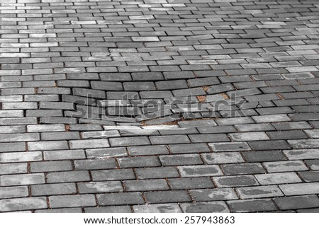 Paving decorative tiles. Poor road. In the middle of the sidewalk collapsed pavement and formed a pit. Dangerous pedestrian traffic - stock photo