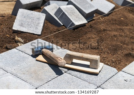Paving grey blocks with instruments in working process - stock photo
