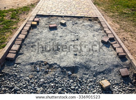 Paving the footpath with the tiled cubes. - stock photo