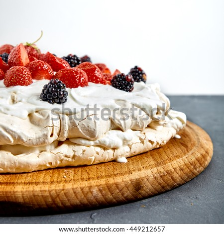Pavlova cake with strawberry and blackberries. Two layers of french meringue and whiped cream with many berries. - stock photo