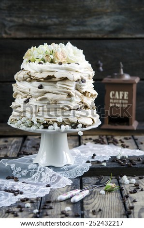 Pavlova with coffee and whipped cream on wooden background - stock photo