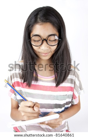 pay attention, Asian girl holding pencil writing on notebook studying. - stock photo
