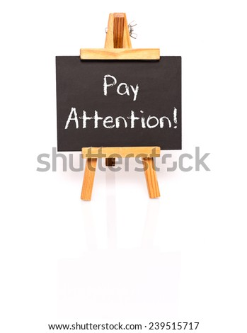 Pay attention. Blackboard with text and easel. Photo on white background with shadow and reflection. - stock photo