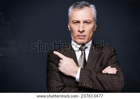 Pay attention to this. Portrait of confident senior man in formalwear looking at camera and pointing away while standing against blackboard - stock photo