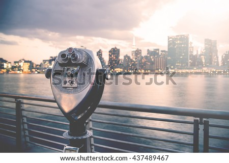 Pay binoculars in Long Island City with the Manhattan skyline at sunset in the background. travel, vacation, sightseeing, new york, tourism, and urban living concept - stock photo